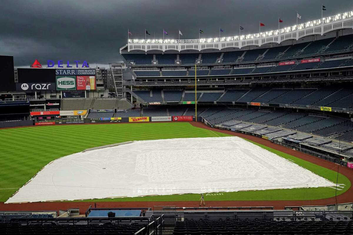 Storm clouds move over a tarp-covered field at Yankee Stadium where a baseball game between the New York Yankees and the Baltimore Orioles has been postponed due to inclement weather, Thursday, Sept. 10, 2020, in New York. The game was rescheduled for Friday afternoon as part of a doubleheader. (AP Photo/Kathy Willens)