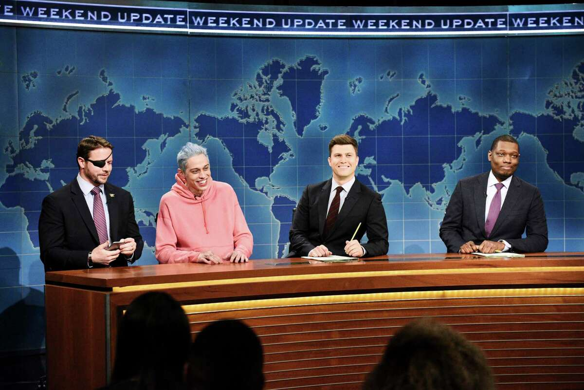 In this Nov. 10, 2018 photo provided by NBC, Lt. Com. Dan Crenshaw, from left, a congressman-elect from Texas, Pete Davidson, Anchor Colin Jost, and Anchor Michael Che appear during Saturday Night Livea€™s