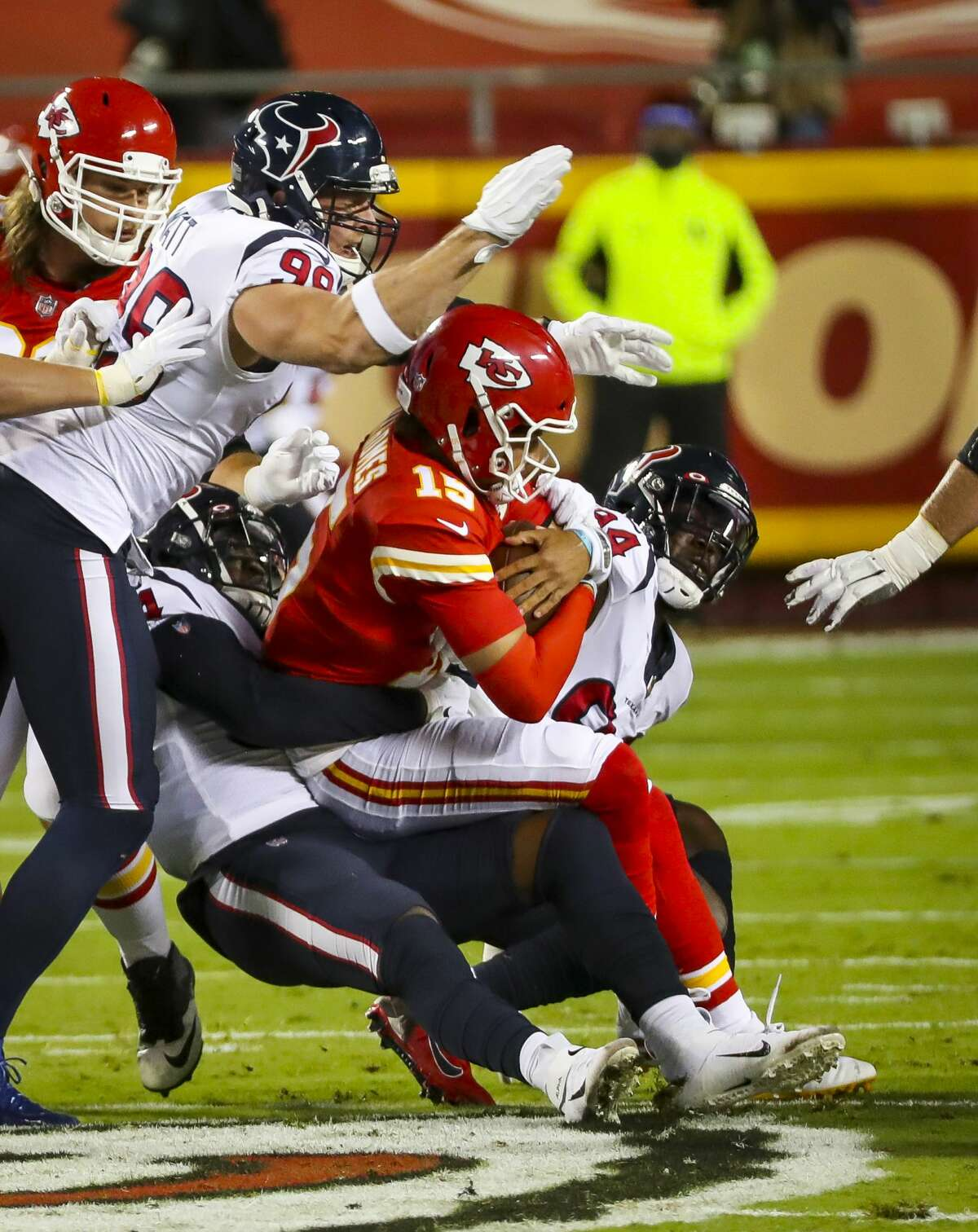 Houston Texans defensive end J.J. Watt (99) helps Houston Texans linebacker Jacob Martin (54) sack Kansas City Chiefs quarterback Patrick Mahomes (15) during the first quarter of an NFL football game on Thursday, Sept. 10, 2020, at Arrowhead Stadium in Kansas City.