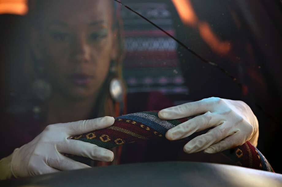 Delon Thurston, 39, poses in her car in a driveway - where she was dragged out of her vehicle and arrested by members of the Vallejo Police Department  - on Tuesday, August 11, 2020, in Vallejo, Calif. The incident happened on Oct. 31, 2018.  Additional info: Thurston sometimes drives home from work wearing disposable plastic gloves. The gloves press an oily therapeutic treatment containing turmeric, black pepper, lavender and coconut oil into her pores, soothing her achy hands and wrists after her shifts as a massage therapist. But to the Vallejo police officers who arrested the masseuse on Oct. 31, 2018, a driver wearing plastic gloves suggested something very different. Thurston was dragged from her car and arrested. The car wasn't stolen. It was hers, and police officers knew it before they took her to jail. Photo: Yalonda M. James / The Chronicle