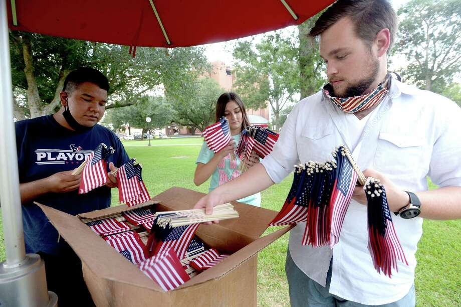 Members of the Lamar University chapter of Young Conservatives of Texas, including Pedro Castelan, Madame Chairman Alexandra Carr, and Devon Carter get ready to place 2, 977 flags outside the Brooks-Shivers Dining Hall Thursday night in remembrance of the lives lost during the terrorist attacks in the U. S. September, 11, 2001. Photo taken Thursday, September 10, 2020 Kim Brent/The Enterprise Photo: Kim Brent / The Enterprise / BEN