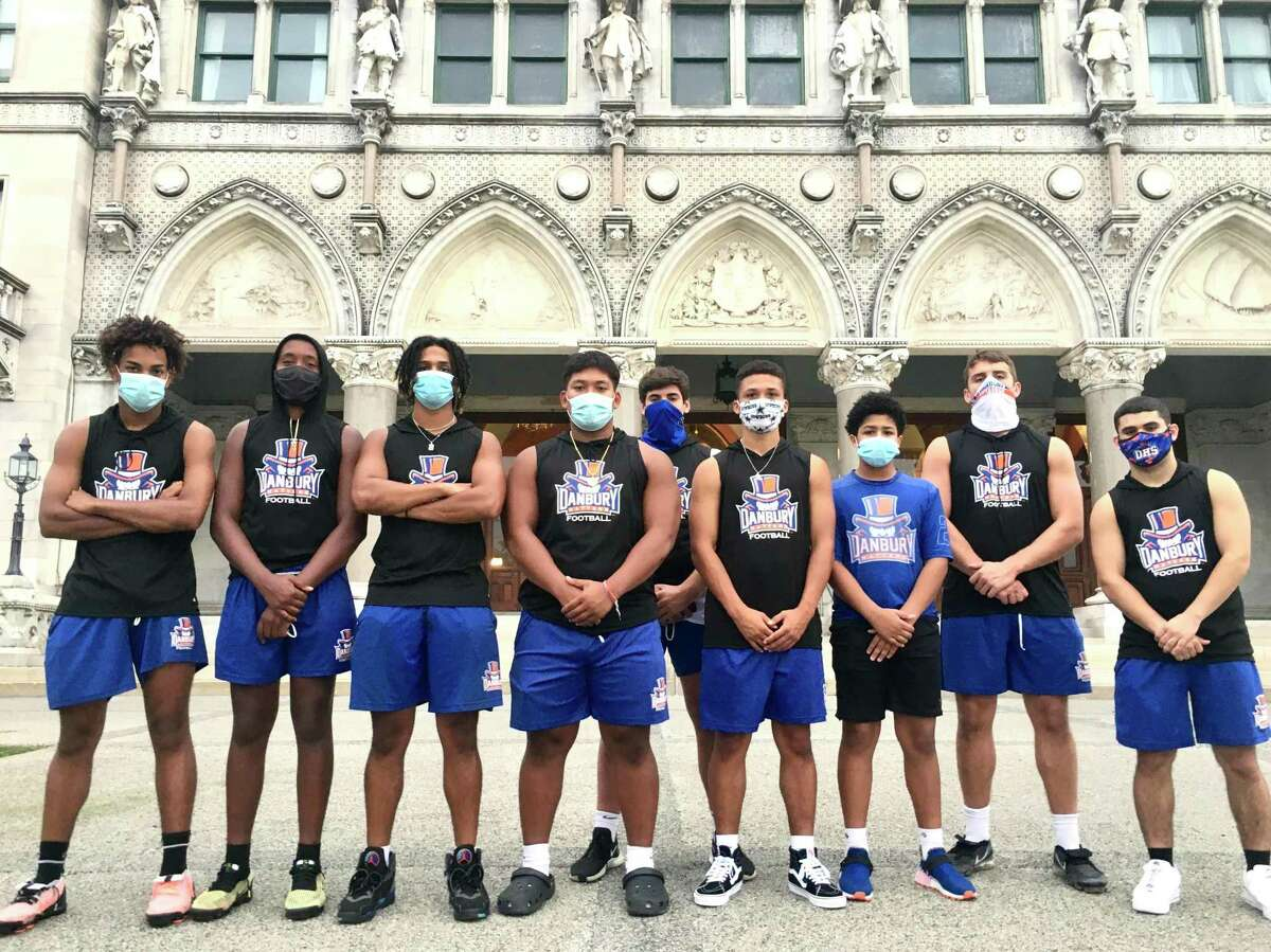 """Members of the Danbury High School football team participated in a rally for a football season a the state Capitol on Wednesday, Sept. 9, 2020. Third from left is Brenyn Boswell, who said,""""I wish they would at least give us a definite 'No.'"""""""