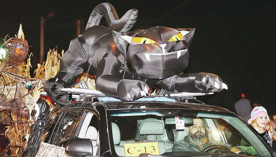 A giant black cat with a moving head adorns the top of a vehicle pulling a float in the 102nd annual Alton Halloween Parade in 2018. For only the seventh time since 1916, the parade will not be held this year because of pandemic precautions.