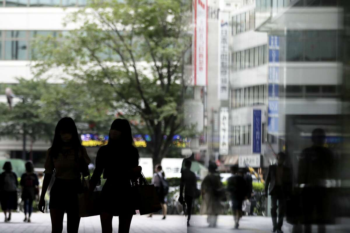 Pedestrians walk along a street in Tokyo, Japan, on Tuesday, July 9, 2019. Photographer: Kiyoshi Ota/Bloomberg
