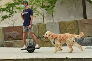 A man rides a Onewheel as he walks a dog along Madison Ave. near the Empire State Plaza on Friday, Sept. 11, 2020 in Albany, N.Y. (Lori Van Buren/Times Union)