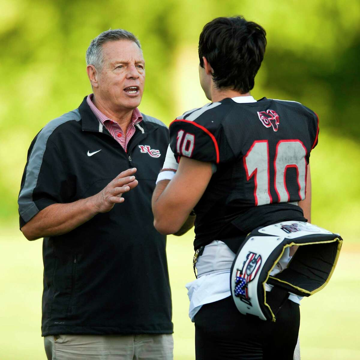 New Canaan coach Lou Marinelli chats with quarterback Drew Pyne during the 11th Annual Brian Wilderman Memorial Red and White football game at Dunning Stadium in New Canaan on June 15, 2018.