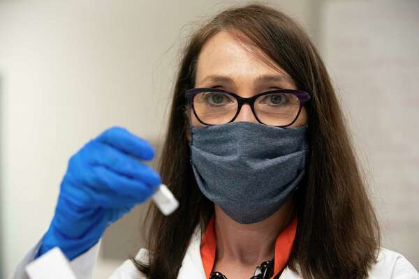Maria Bottazzi, co-director of Texas Children's Hospitals Center for Vaccine Development, holds a vial of vaccine for COVID-19 that is developed in the lab Thursday, June 18, 2020, in Houston. The lab has been working to develop vaccine for COVID-19 with yeast.