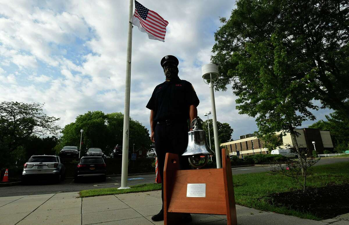 Firefighter George Baez tolls the bell in rememberance for the local victims as the City of Norwalk holds its annual 9/11 Remembrance Ceremony outside of City Hall Friday, September 11, 2020, in Norwalk, Conn. The mayor led the ceremony with members of the police and fire departments in attendance.