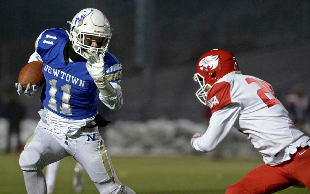 Newtown's Miles Ricks (11) goes around NFA's Nathan Cote in the Class LL State Football Quarterfinal game between Norwich Free Academy and Newtown high schools in December 2019 in Newtown.