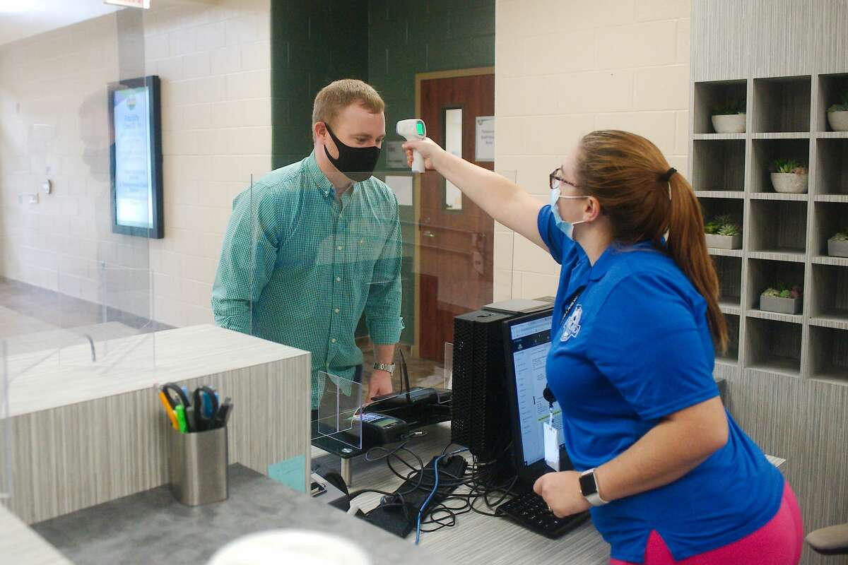 Pearland Recreation Center Operations Manager Kyle Livesay has his temperature measured as Stasey Bickham demonstrates the screening process for staff and patrons as they enter the center.