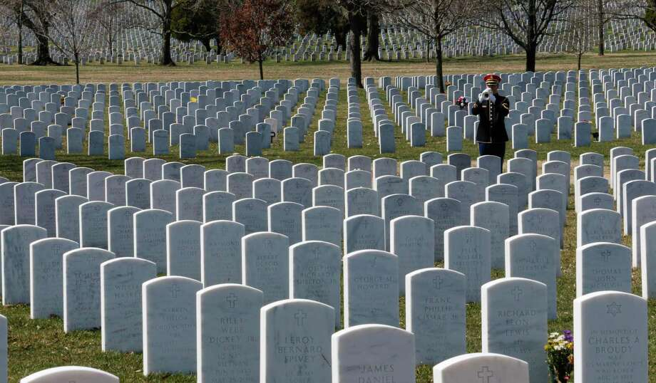 A military bugler plays taps during a funeral at Arlington National Cemetery in Arlington, Va. Photo: Associated Press / Copyright 2019 The Associated Press. All rights reserved.