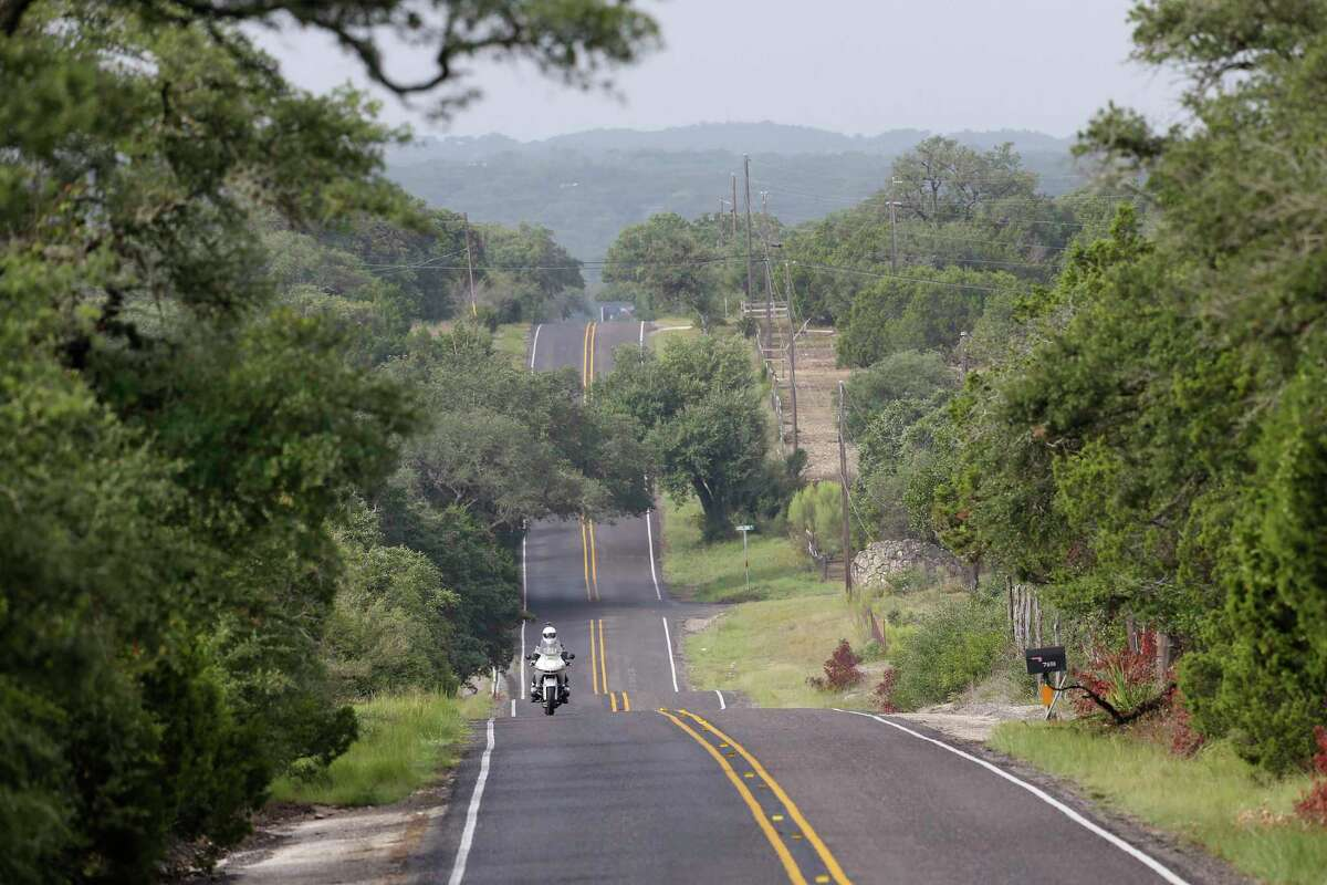A cyclist rides east on Park Road 37 between Medina Lake and Texas 16 on the Medina Lake, northern route.