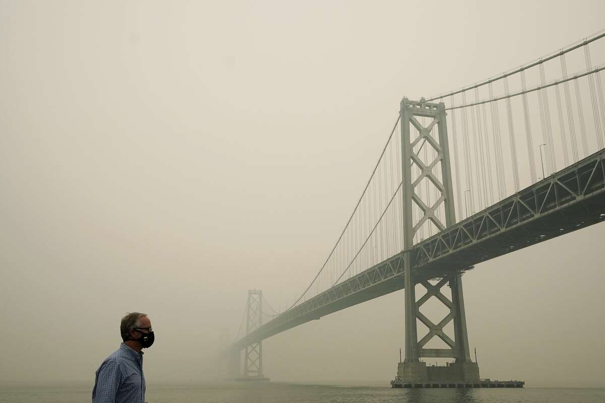 Smoke and haze from wildfires partially obscures the view of the San Francisco-Oakland Bay Bridge along the Embarcadero in San Francisco, Thursday, Sept. 10, 2020.