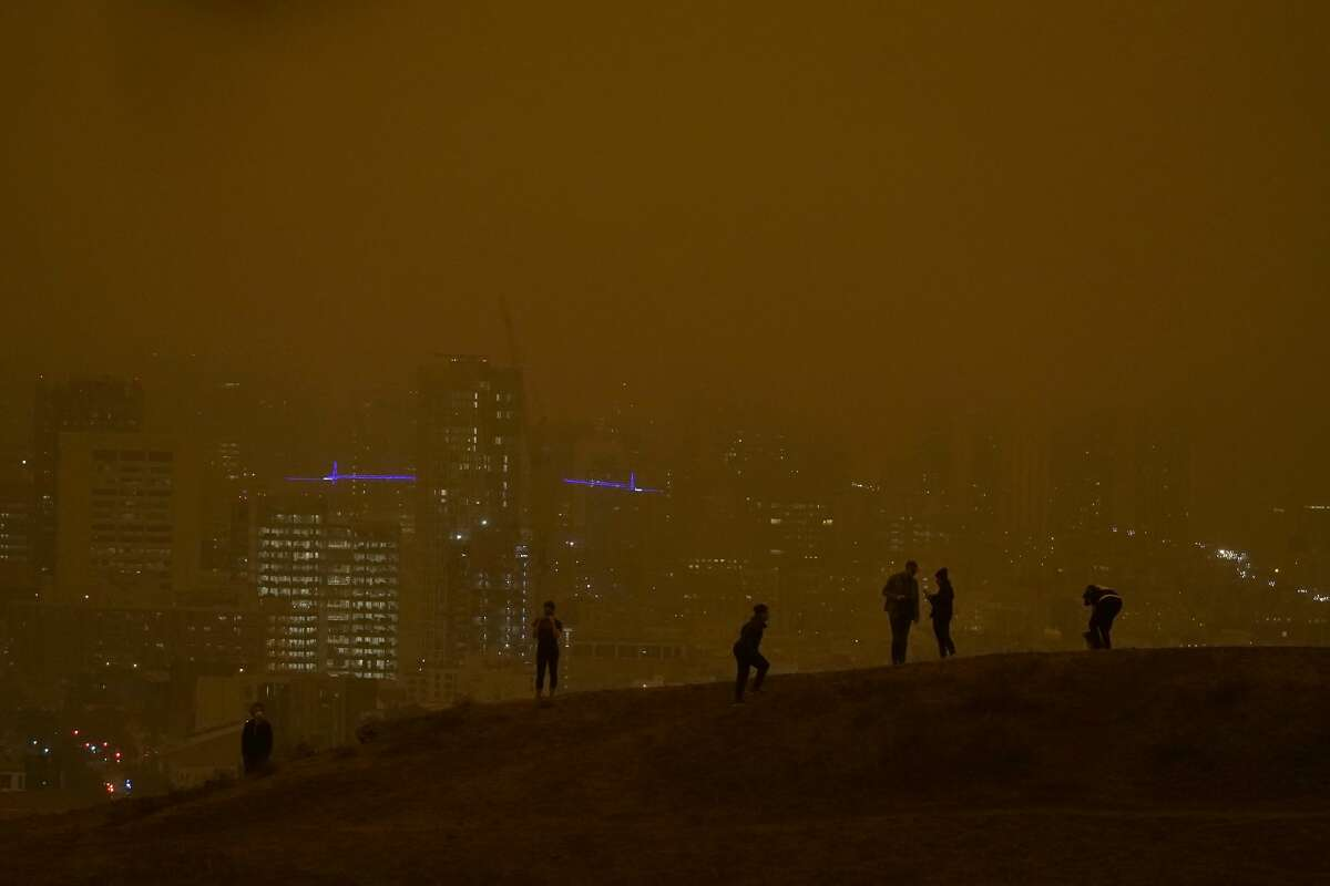 People look toward the skyline obscured by wildfire smoke during daylight hours from Kite Hill Open Space in San Francisco, Wednesday, Sept. 9, 2020.