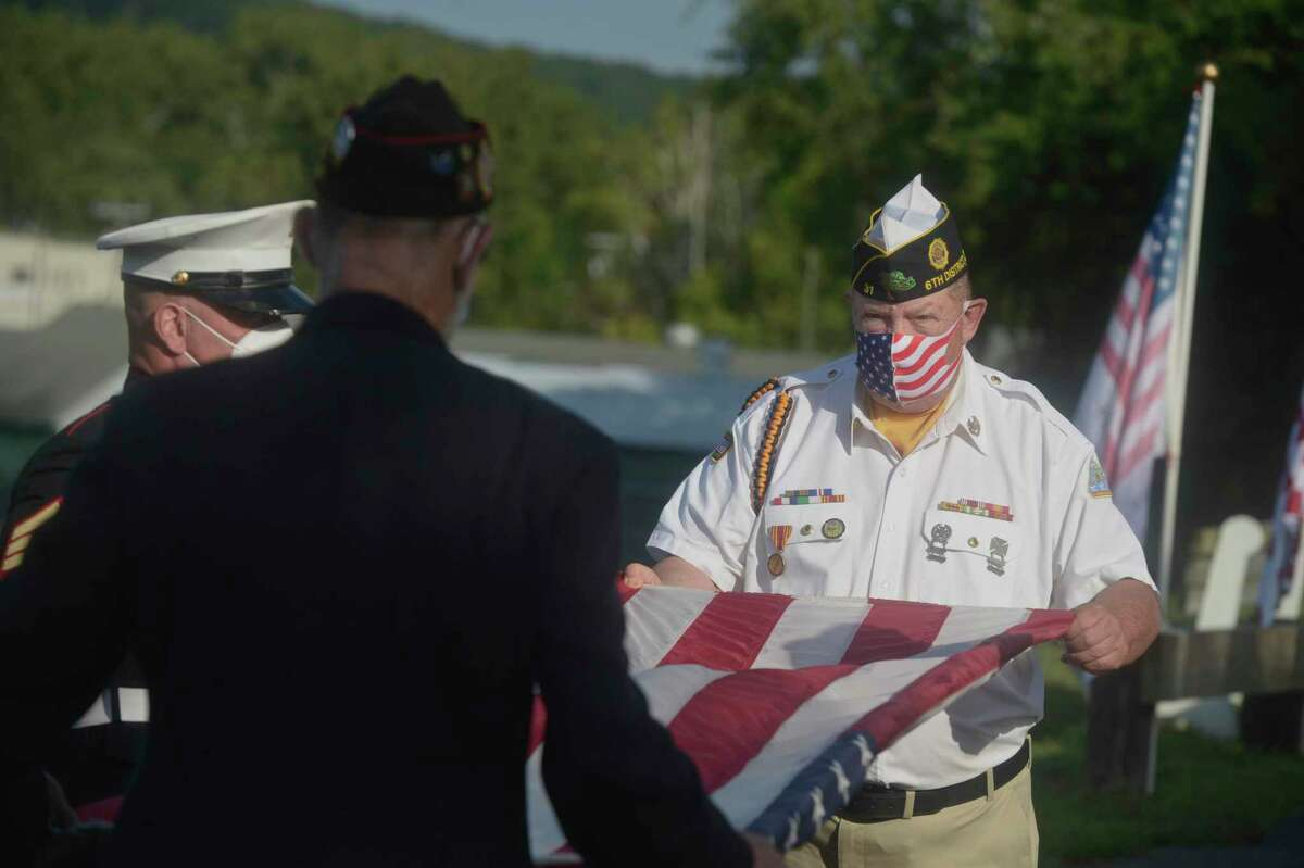 Jeffrey McBreairty, right, American Legion Commander Post 31, folds the flag with assistance from Jim Delancy, VFW Commander New Milford Post 1672, during the memorial ceremony to mark the19th anniversary of September 11, 2001. Friday, September 11, 2020, in New Milford, Conn. State Sen. Craig Miner, whose district includes New Milford, also drew comparisons to the coronavirus and the loss people are feeling today.