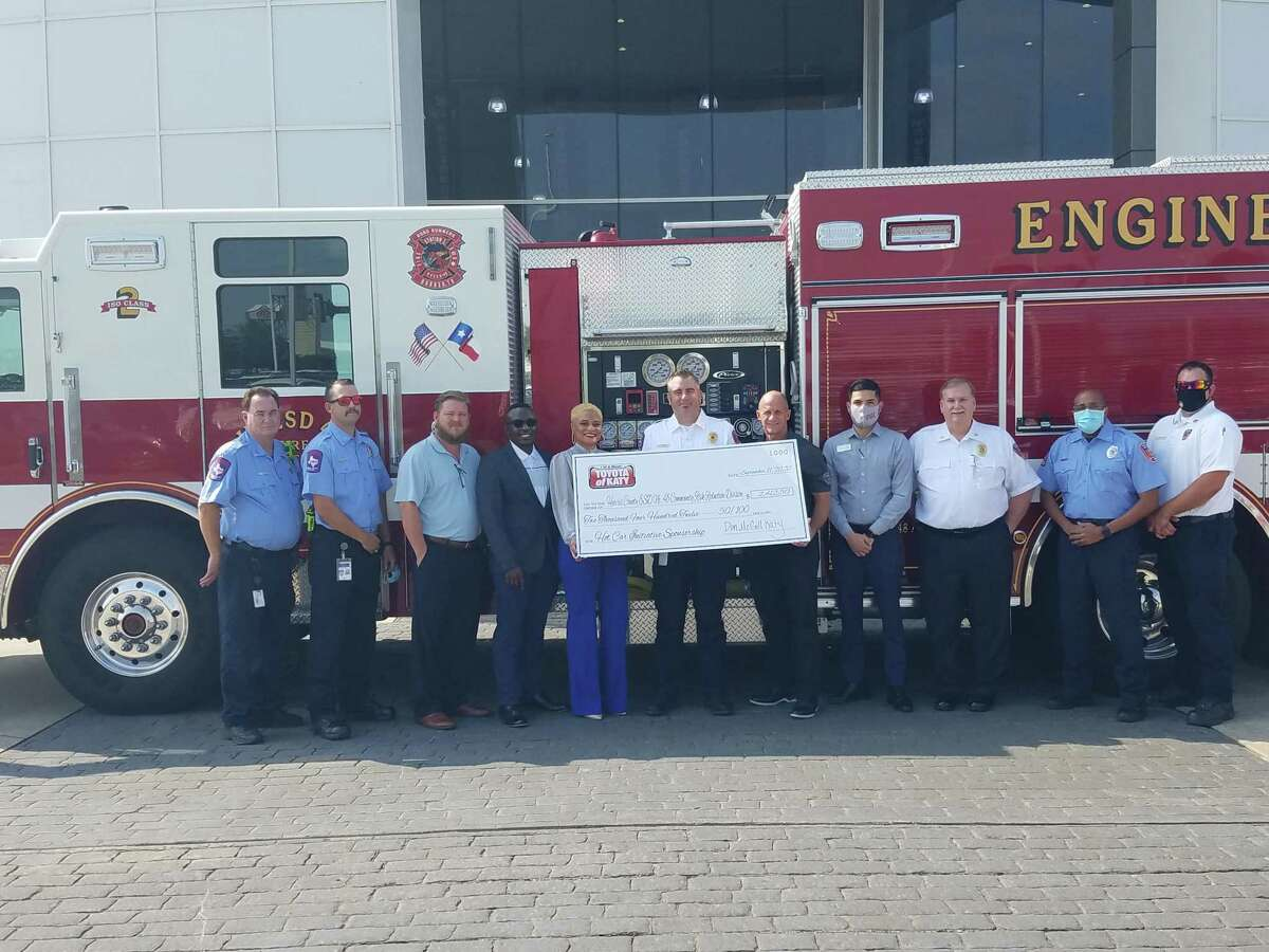 Representatives from HCESD 48 accept a check from Toyota of Katy for half the cost of the hot car initiative display on Sept. 11.