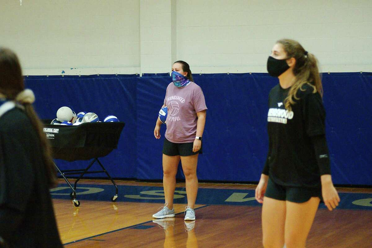 Volleyball coach Sarah Paulk watches as the team participates in a drill.