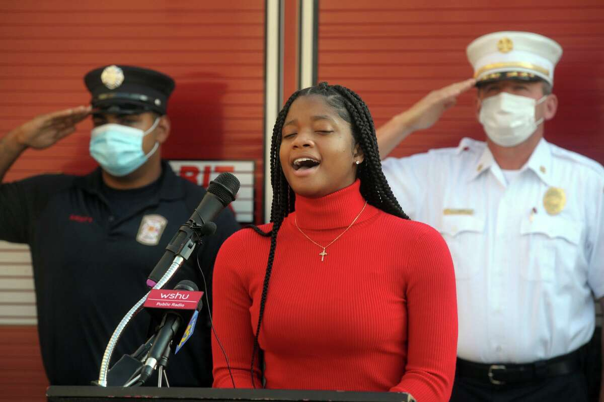Imani Tyson from Great Oaks Charter School sings the National Anthem during the 9/11 remembrance ceremony at Fire Headquarters, in Bridgeport, Conn. Sept. 11, 2020.