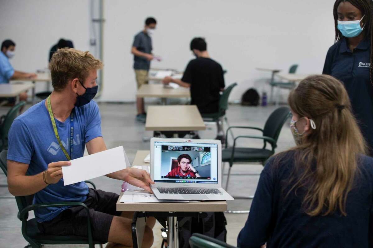 Rice student Ethan Kelly, left, works with teaching assistant Derin Okunubi, far right, and Emily Ellison during an engineering lab in one of the recently built temporary buildings on the Rice University campus on Wednesday, Sept. 2, 2020 in Houston. The temporary buildings have been brought to the campus to help with social distancing during classes amid the coronavirus pandemic.
