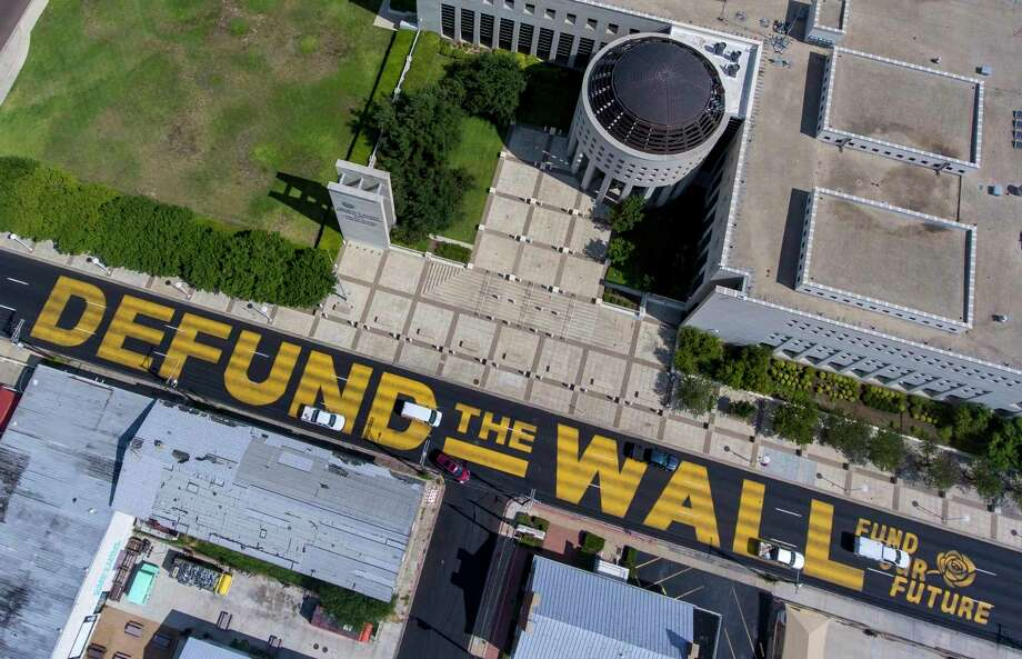 Giant, yellow letters, seen Tuesday, Aug. 18, 2020, painted on Victoria Street in front of the federal courthouse in Laredo Sunday, Aug. 16, 2020 read ÒDefund the Wall Fund our FutureÓ. Photo: William Luther, Staff / Staff / ©2020 San Antonio Express-News