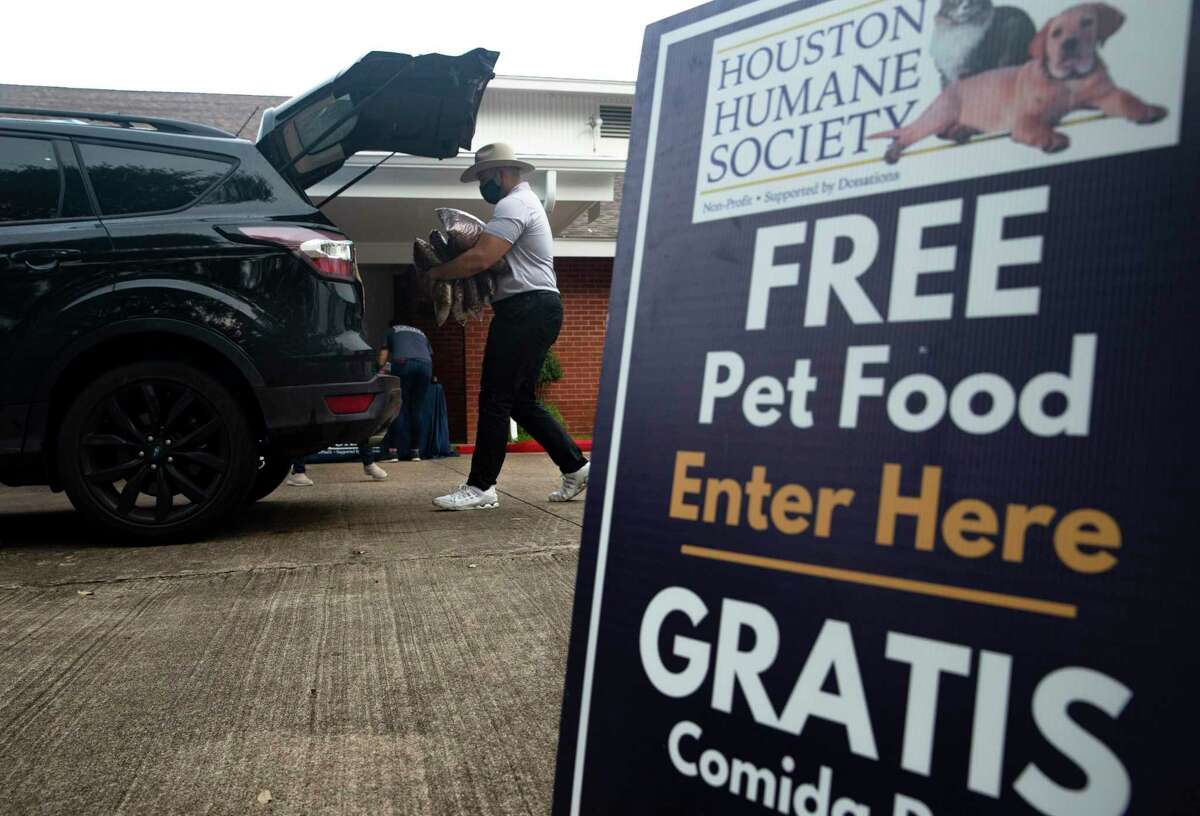 Houston City Council District J Constituent Services Director David Alexander Brizuela helps loading pet food at a giveaway with the Houston Humane Society Thursday, Sept. 10, 2020, in Houston. Council member Edward Pollard's office used the pet food distribution as an opportunity to get people to fill out the 2020 Census.