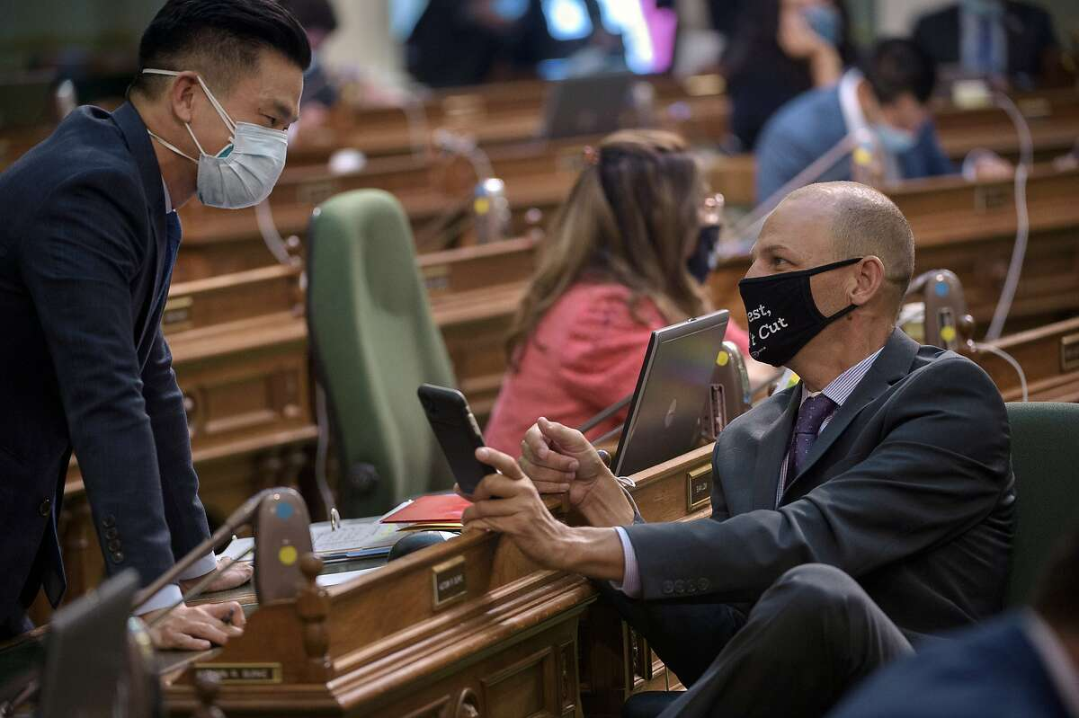 Assemblymember Evan Low, D-Cupertino, left, speaks with Assemblymember Kevin McCarty, D-Sacramento, on the Assembly floor at the Capitol in Sacramento, Calif., Tuesday, Aug. 25, 2020. (AP Photo/Randall Benton)