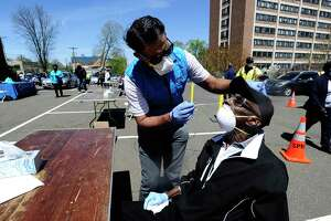 Dr. JD Sidana of DOCS Urgent Care Stamford administers a COVID-19 nasal swab test on Robert Hayes, 73, of Stamford at a walk up testing site for the Coronavirus at AME Bethel Church in Stamford, Connecticut on May 2, 2020. Over 200 tests were perform by medical professinals for residents of Stamford's Westside.