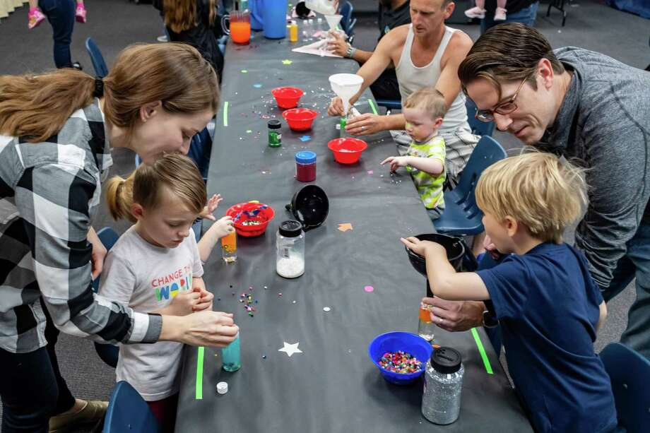 Children fill their sensory bottles with sparkles, beads and crystals which withal glow in the dark. The Beaumont Children's Museum hosted Glow Mania on Saturday, December 28, 2019 with a variety of glowing activities for children. Fran Ruchalski/The Enterprise Photo: Fran Ruchalski/The Enterprise
