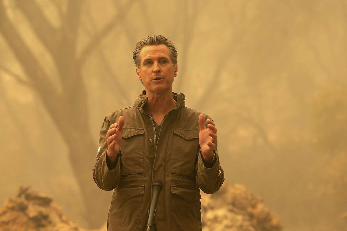 """California Gov. Gavin Newsom speaks to the media after he toured the North Complex Fire zone in Butte County on Friday, Sept. 11, 2020, outside of Oroville, Calif. Gov. Gavin Newsom toured the fire-ravaged region Friday and strongly asserted that climate change was evident and pledged to redouble efforts to """"decarbonize"""" the economy. (Paul Kitagaki Jr./The Sacramento Bee via AP, Pool)"""