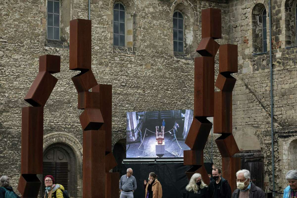 A screen outside the St. Burchardi church shows spectators a chord changing event to the organ inside, in Halberstadt, Germany, Sept. 5, 2020. The long, slow performance of a piece by the American composer John Cage is scheduled to run until 2640 a€?