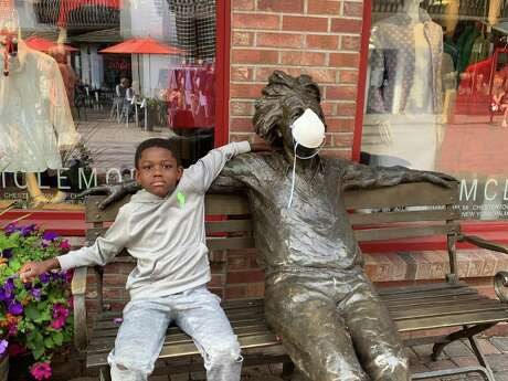 Roslyn Bazzelle Mitchell's son hangs out with a masked statue in Vail, Colo.