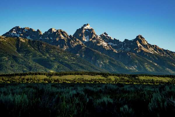 The Teton Range, a mountain range of the Rocky Mountains, is seen as the sun rises in Moose, Wyoming, United States at the Teton Point Turnout on July 13, 2018. It is south of Yellowstone National Park and most of the east side of the range is within Grand Teton National Park.