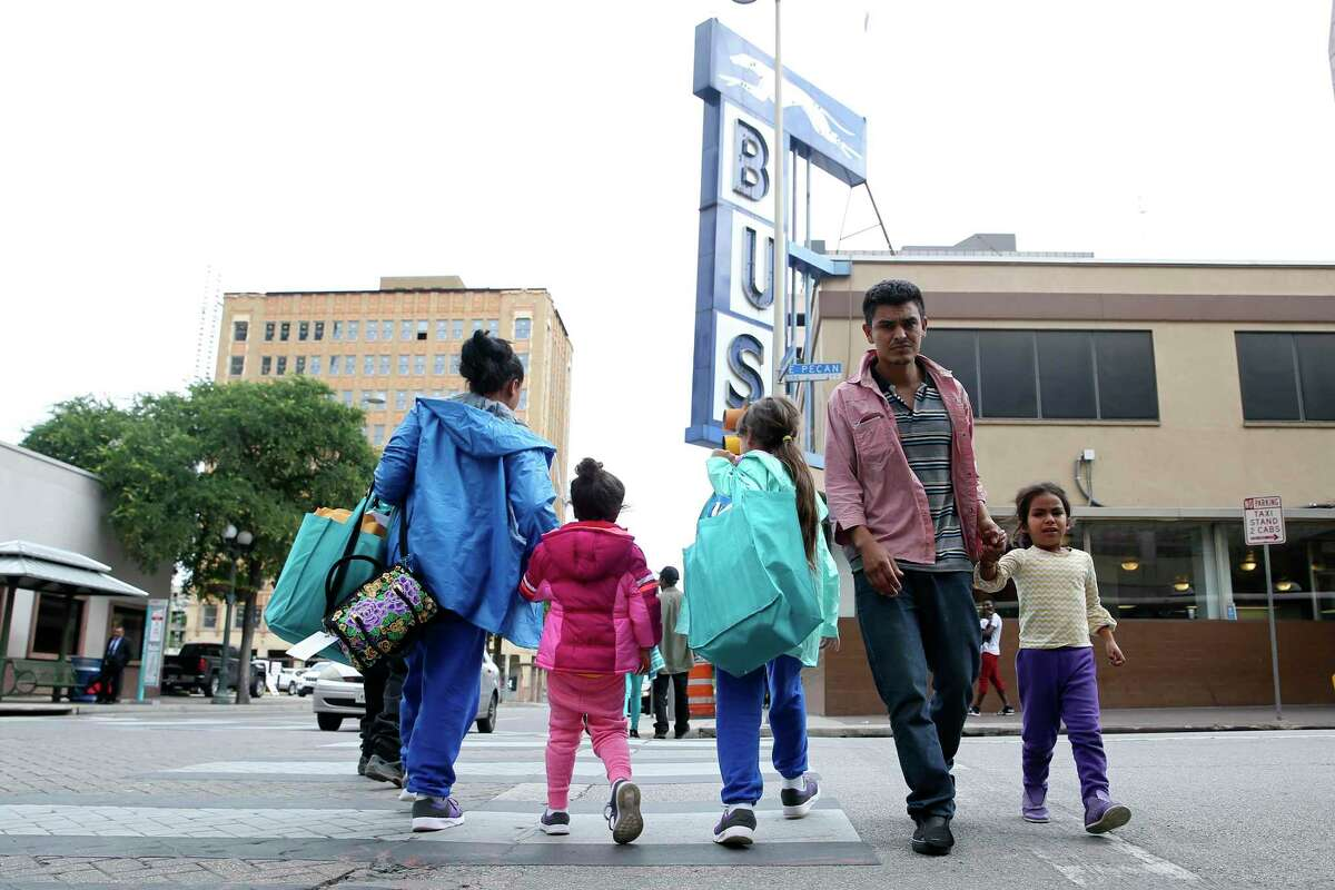 Migrants make their way between the Greyhound Station, background, and the City of San Antonio Resource Center, Wednesday, May 15, 2019. The Resource Center, which opened on March 30, provides humanitarian help to the mostly Central American migrants. According to City Manager Erik Walsh, U.S. Customs and Border Protection has notified the city that they are expecting an increase of migrants making their way through San Antonio to points throughout the U.S.