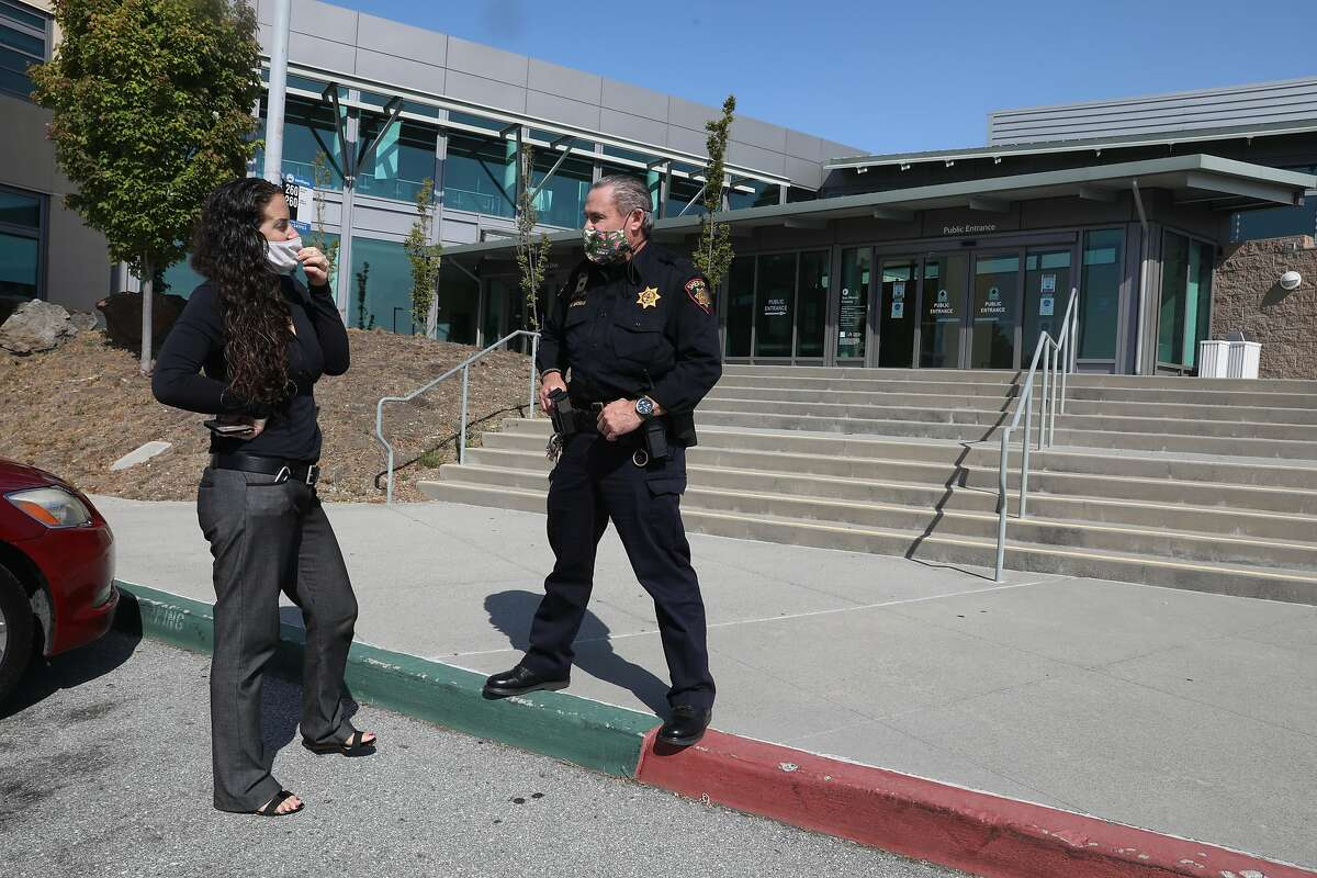 Deputy probation officer Diana Chilicas (left) talks with deputy Grogan (middle) at the entrance to the San Mateo juvenile hall seen on Thursday, Sept. 3, 2020, in San Mateo, Calif.