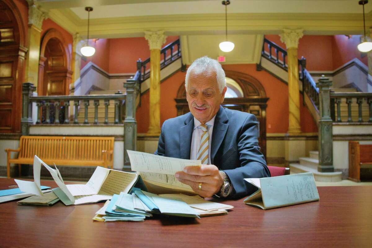 Rensselaer County Clerk Frank Merola looks over Legs Diamond's court records while sitting on the first floor of the Rensselaer County Court House on Tuesday, Sept. 1, 2020, in Troy, N.Y. (Paul Buckowski/Times Union)