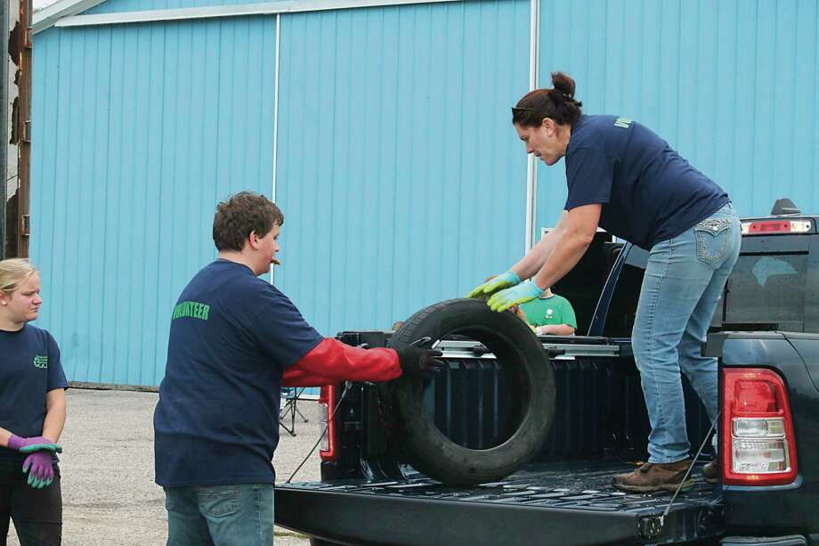 Volunteers unload scrap tires from a truck in September 2019 during the Manistee County tire collection event. (File photo)