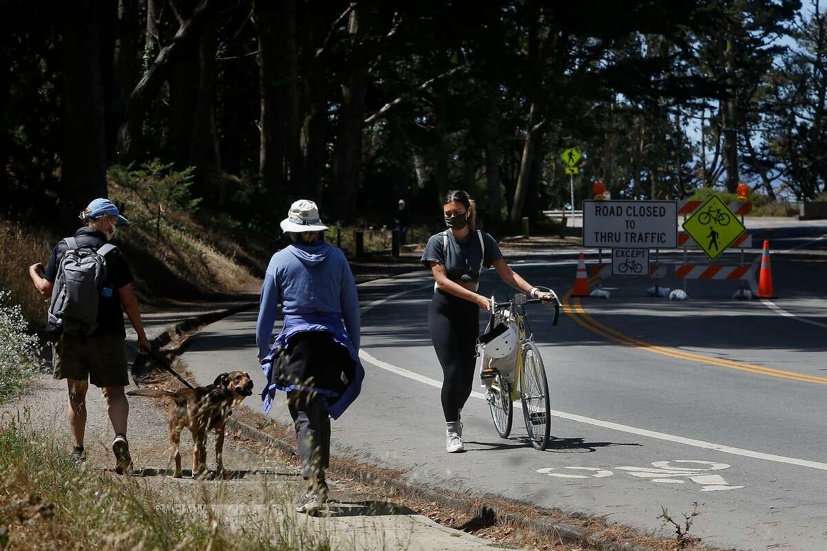 Jenna Mansy (right) of San Francisco, walks with her bike after it had a flat tire while she was out for a ride while pedestrians walk past along Washington Boulevard in a slow street zone in the Presido on Wednesday, July 22, 2020 in San Francisco, Calif. Mansy said the slow streets feel alot safer to ride.