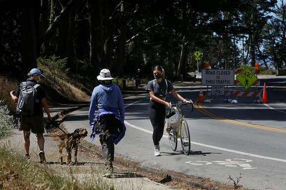 """Jenna Mansy (right) of San Francisco, walks with her bike after it had a flat tire while she was out for a ride while pedestrians walk past along Washington Boulevard in a slow street zone in the Presido on Wednesday, July 22, 2020 in San Francisco, Calif.  Mansy said the slow streets feel alot safer to ride. """"It's a lot of fun to see the bikers. It feels like you're interacting even though you're alone."""""""