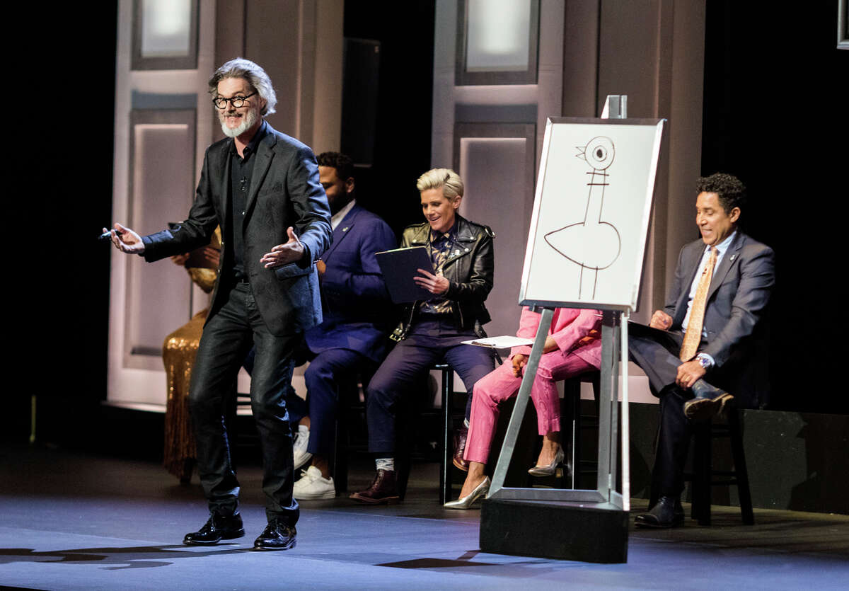 This image released by HBO Max shows author and illustrator Mo Willems, standing, in a€œDona€™t Let the Pigeon Do Storytime!a€ The special was filmed last year at the Kennedy Center and features comedy inspired by Willemsa€™ books for children. (HBO Max via AP)