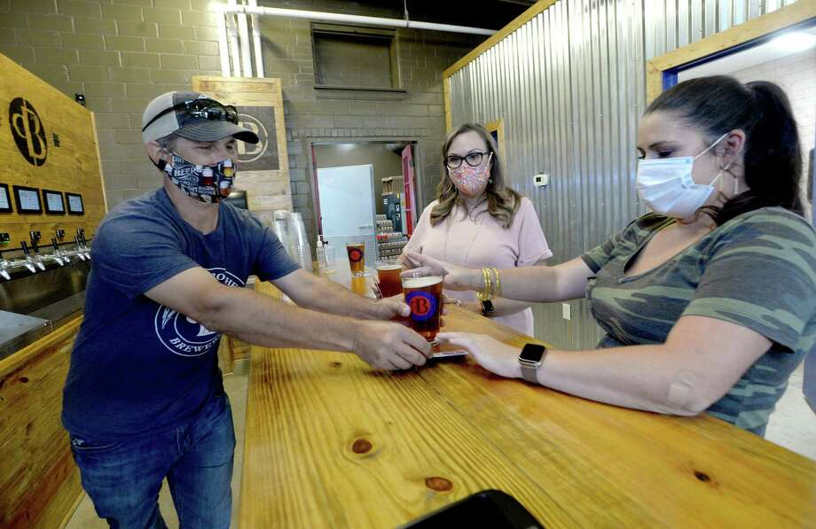 Joel Hollier serves up brews to Lauren Martin and Beth Rogers as they have lunch and brews at Pour Brothers Brewery in Beaumont, one of the establishments which reopened Friday after getting a license change from the TABC days ago. Photo taken Friday, September 11, 2020 Kim Brent/The Enterprise Photo: Kim Brent / The Enterprise / BEN