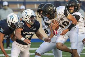Andrews' E.J. Lopez tries to make more yards as Greenwood's Drew Crunk chases 09/11/2020 at Grande Communications Stadium. Tim Fischer/Reporter-Telegram