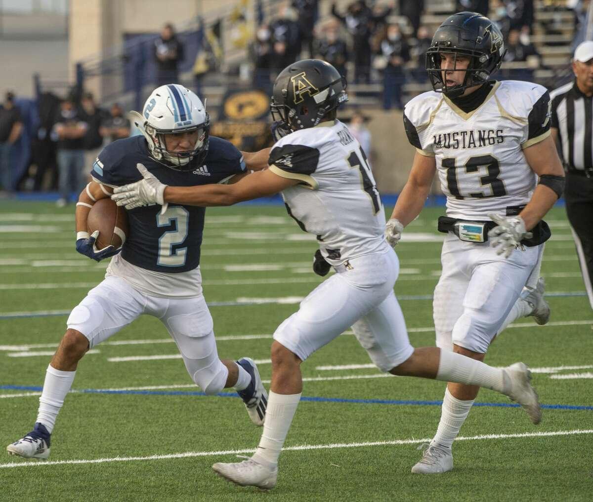 Greenwood's Izaiah Ramirez tries to get away from Andrews' Jose Bustamante and AJ Britten, 13, 09/11/2020 at Grande Communications Stadium. Tim Fischer/Reporter-Telegram