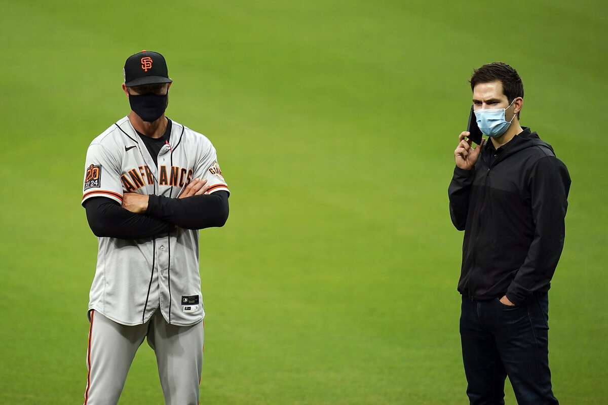 San Francisco Giants general manager Scott Harris, right, speaks on a phone alongside manager Gabe Kapler after their baseball game against the San Diego Padres was postponed Friday, Sept. 11, 2020, in San Diego. The game was postponed minutes before the scheduled first pitch after someone in the Giants organization tested positive for COVID-19. (AP Photo/Gregory Bull)