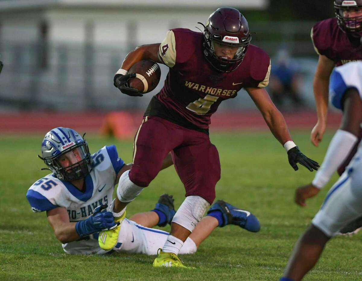 Running back Buddy Santos of Devine escapes the grasp of Randolph's Carson Morris (55) during high school football action at Warhorse Stadium on Friday, Sept. 11, 2020.
