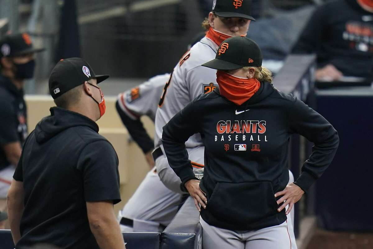 San Francisco Giants assistant coach Alyssa Nakken, right, and other team members linger after the team's baseball game against the San Diego Padres was postponed Friday, Sept. 11, 2020, in San Diego, minutes before the scheduled first pitch after someone in the Giants organization tested positive for COVID-19. (AP Photo/Gregory Bull)