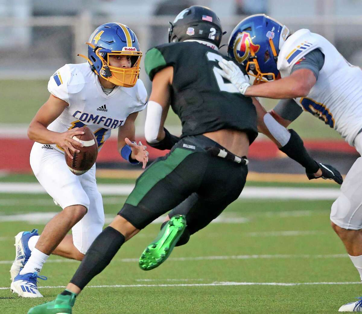 Bobcat quarterback Oscar Falcon looks for an escape route from the rush of Jayden Williams as Marion hosts Comfort at Veterans Stadium in high school football on Sept. 11, 2020.