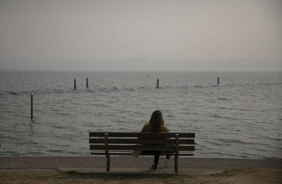 SEATTLE, WA - SEPTEMBER 11: A woman sits on a bench at Madison Park Beach as smoke from wildfires on the West Coast fills the air on September 11, 2020 in Seattle, Washington. According to reports, air quality is expected to worsen as smoke from dozens of wildfires in forests of the Pacific Northwest and along the West Coast descends onto the region. (Photo by Lindsey Wasson/Getty Images) Photo: Lindsey Wasson/Getty Images / 2020 Getty Images