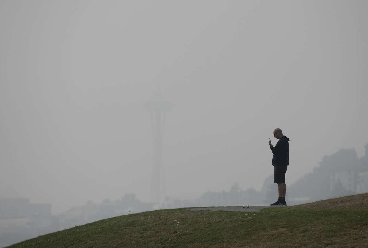 SEATTLE, WA - SEPTEMBER 11: The Space Needle is almost completely obscured by smoke from wildfires as a man talks on his phone at Gas Works Park on September 11, 2020 in Seattle, Washington. According to reports, air quality is expected to worsen as smoke from dozens of wildfires in forests of the Pacific Northwest and along the West Coast descends onto the region. (Photo by Lindsey Wasson/Getty Images)