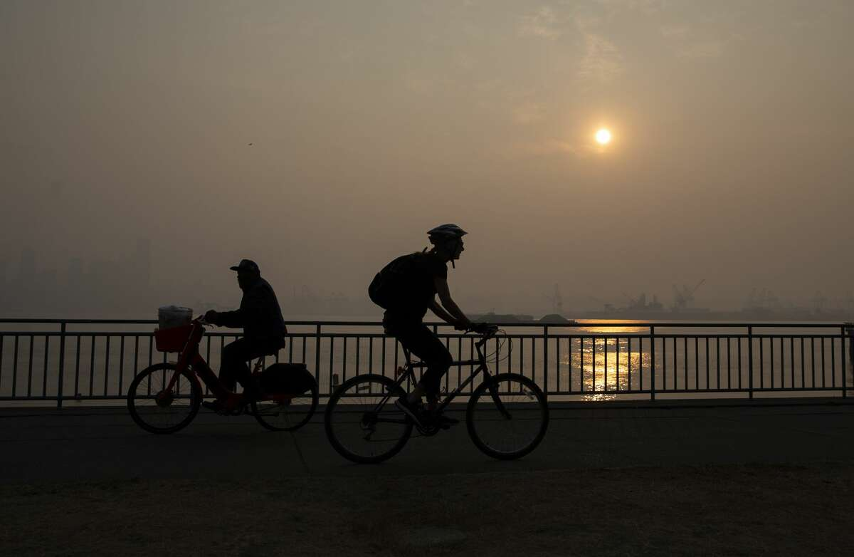 People bike along Harbor Avenue SW in West Seattle as smoke from wildfires fills the air on September 11, 2020 in Seattle, Washington. According to reports, air quality is expected to worsen as smoke from dozens of wildfires in forests of the Pacific Northwest and along the West Coast descends onto the region.