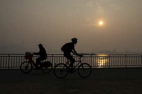 SEATTLE, WA - SEPTEMBER 11: People bike along Harbor Avenue SW in West Seattle as smoke from wildfires fills the air on September 11, 2020 in Seattle, Washington. According to reports, air quality is expected to worsen as smoke from dozens of wildfires in forests of the Pacific Northwest and along the West Coast descends onto the region. (Photo by Lindsey Wasson/Getty Images)
